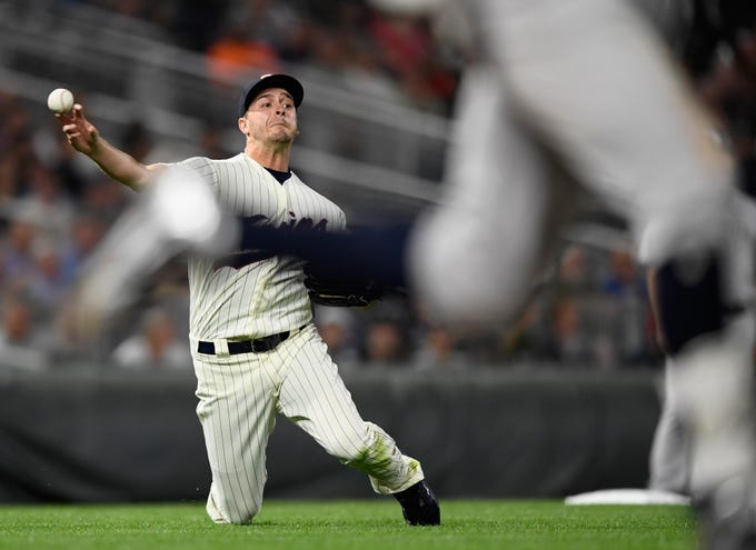 MINNEAPOLIS, MN - SEPTEMBER 12: Jake Odorizzi #12 of the Minnesota Twins makes a play to get out Didi Gregorius #18 of the New York Yankees at first base during the fifth inning of the game on September 12, 2018 at Target Field in Minneapolis, Minnesota.