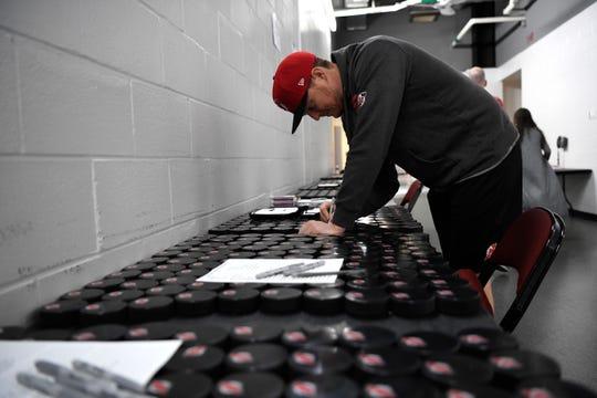 New Jersey Devils goalie Cory Schneider signs hockey pucks during media day at the Prudential Center in Newark, NJ on Thursday, September 13, 2018.