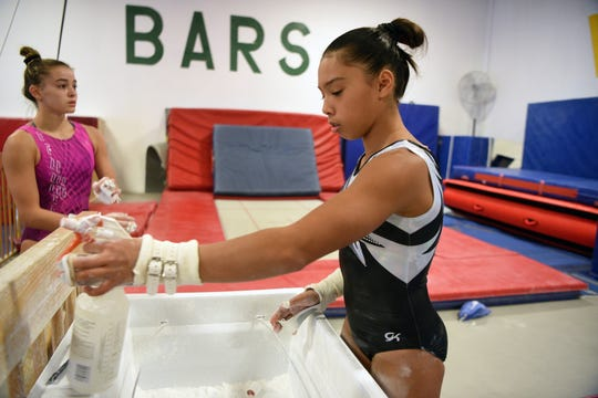 Corinne Bunagan 15, of Ramsey, on right, a member of the Philippines National Gymnastics Team, is competing in the 48th Annual Artistic World Gymnastic Championships in Doha, Qatar beginning on October 25, 2018. Bunagan and Olivia Dunn 15, of Hillsdale, a member of the USA National Team train with their coach, Craig Zappa at ENA Gymnastics in Paramus on Thursday, September 13, 2018.