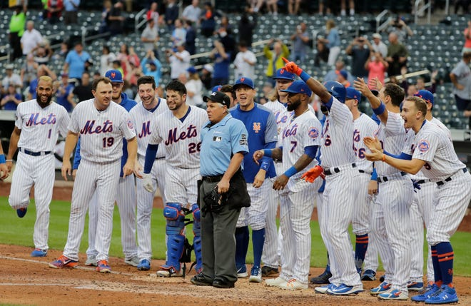 New York Mets players wait for teammate Todd Frazier to arrive at home plate after hitting a walkoff home run during the ninth inning of the first baseball game of a doubleheader against the Miami Marlins, Thursday, Sept. 13, 2018, in New York.