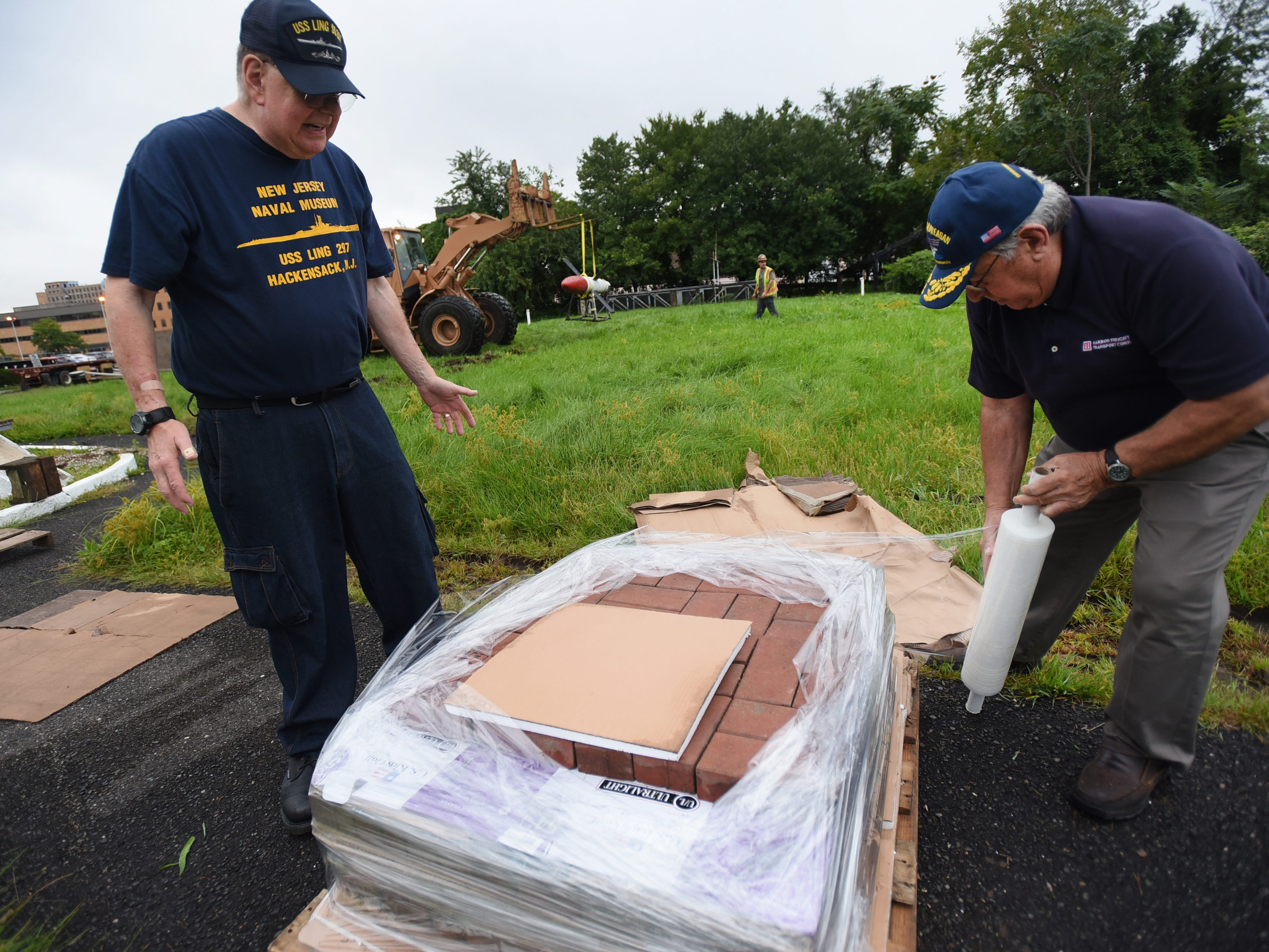 Joseph N. Mattio (R) from Harbor Freight Transport Corp. wraps WWII Memorial for the 52 US Submarines lost in WWII to be removed as Les Altschuler (L) Vice President of NJ Naval Museum and Director of North East Region of USSVI, looks on at the site of the NJ Naval Museum in Hackensack on 09/12/18.  The 1945 USS Ling SS297, 312 foot long submarine remains at the site.