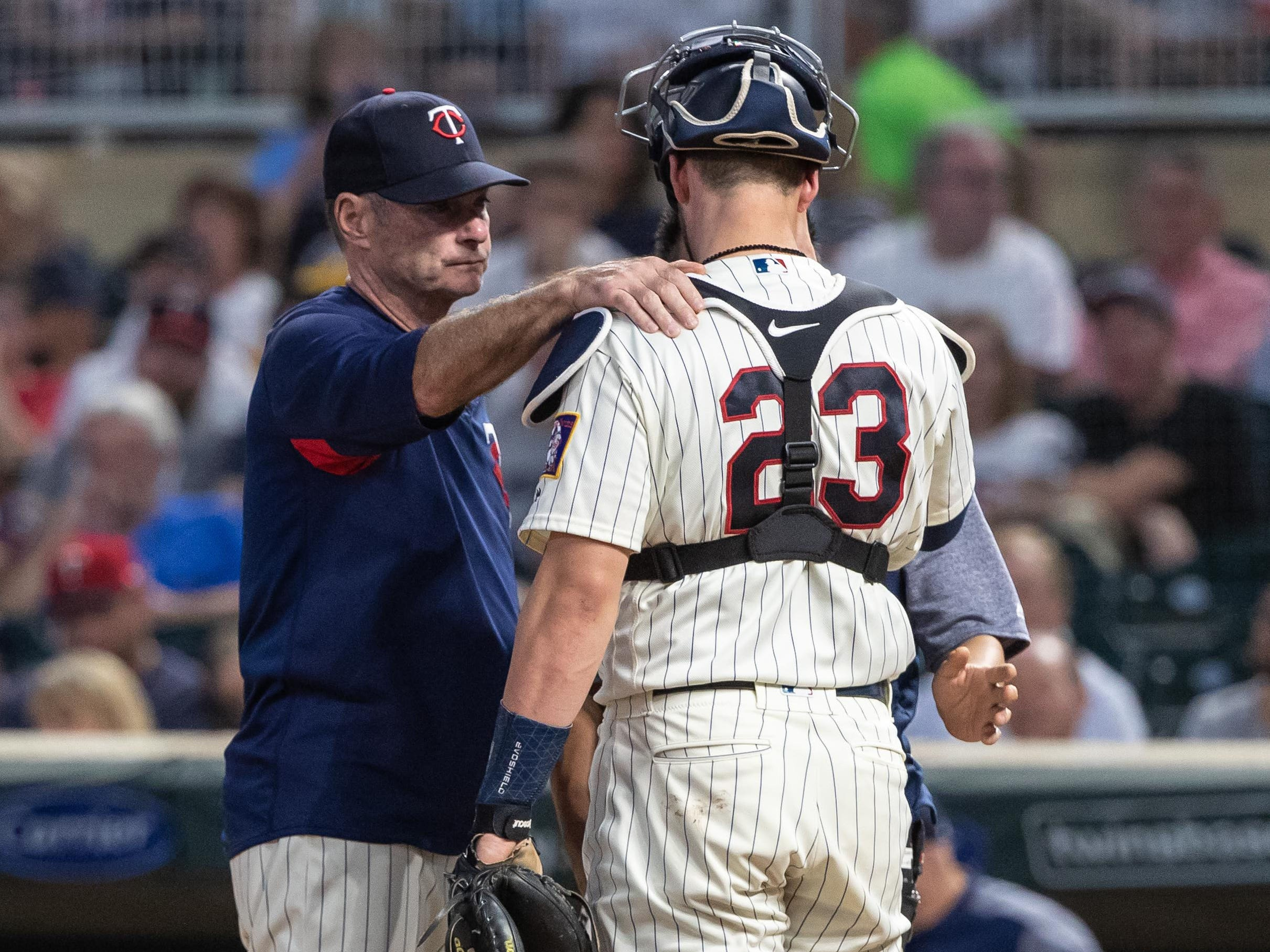 Sep 12, 2018; Minneapolis, MN, USA; Minnesota Twins manager Paul Molitor (4) speaks with catcher Mitch Garver (23) after being hit in the mask with a foul ball during the second inning against the New York Yankees at Target Field.