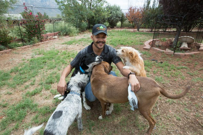 Kwamé Ponschock surrounded by his dogs at his home on the East Mesa on Friday, Sept. 7.