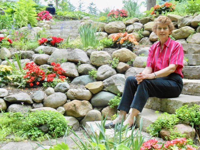 Julie Dawson sits among the beautiful flowers of her garden. She is being honored with the Cultural Arts Award for her work as an ambassador for arts and culture.