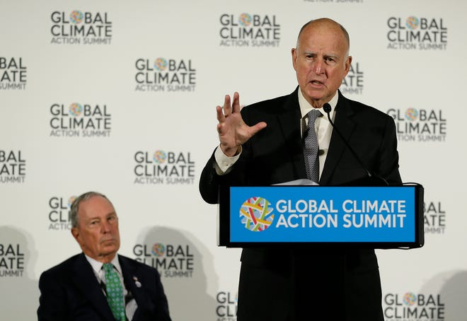 California Gov. Jerry Brown speaks as Michael Bloomberg, left, listens during a news conference at the Global Action Climate Summit in San Francisco on Sept. 13, 2018.