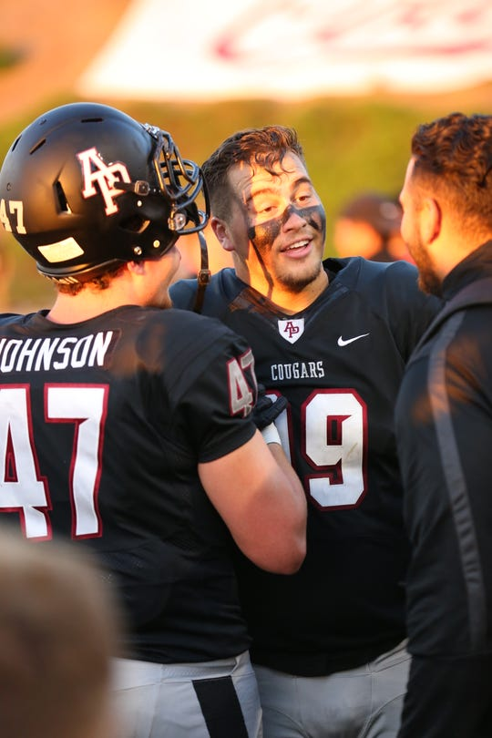 Robbie Polimeni laughs on the sideline after his interception return for a touchdown for Azusa Pacific last Saturday.