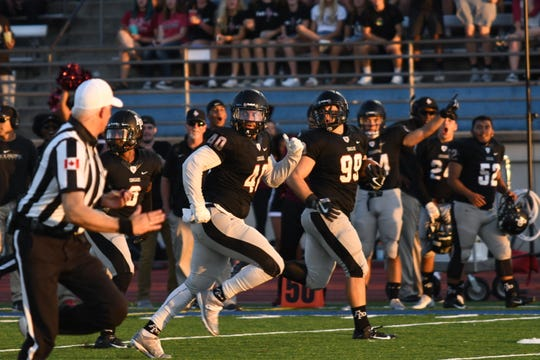 La Quinta graduate and former COD player Robbie Polimeni (99) runs with the ball after an interception for Azusa Pacific on Saturday.