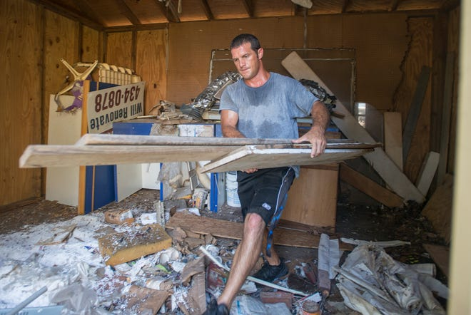 Teen Challenge worker Corbin Gainey removes items from the shed behind a newly acquired Gulf Coast Kid's House building in Pensacola on Thursday, September 13, 2018.  Instead of paying a disposal service to clean out the new building and shed, Teen Challenge donated their services and will be selling any usable items in their thrift shop.