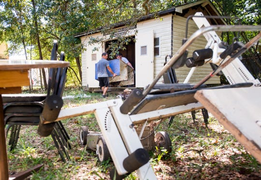 Teen Challenge workers Corbin Gainey, left, and Daniel Brooker remove items from the shed behind a newly acquired Gulf Coast Kid's House building in Pensacola on Thursday, September 13, 2018.  Instead of paying a disposal service to clean out the new building and shed, Teen Challenge donated their services and will be selling any usable items in their thrift shop.