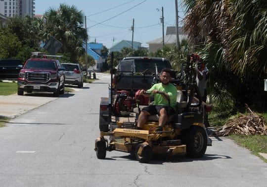 Landscaper Danny Urbio parks his truck and trailer Thursday at a Pensacola Beach roadside.