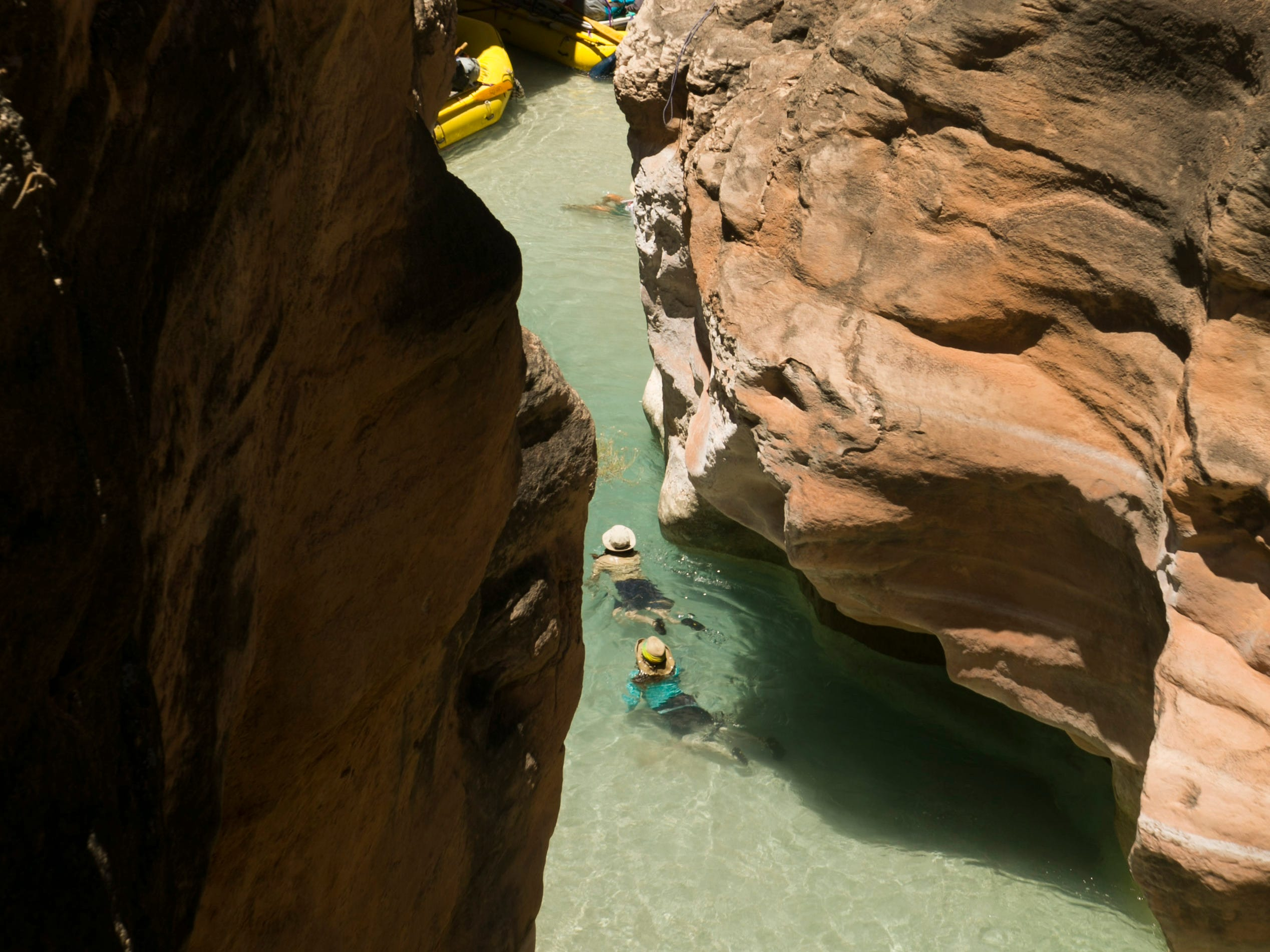 River runners exit the narrows of Havasu Creek to their boats at the confluence of the Colorado River in Grand Canyon National Park. Havasu Creek gets its aqua-blue color from the calcium carbonate in the water. Hundreds of side canyon drainages meet the Colorado River in Grand Canyon and offer a glimpse into something not impacted by Glen Canyon Dam.