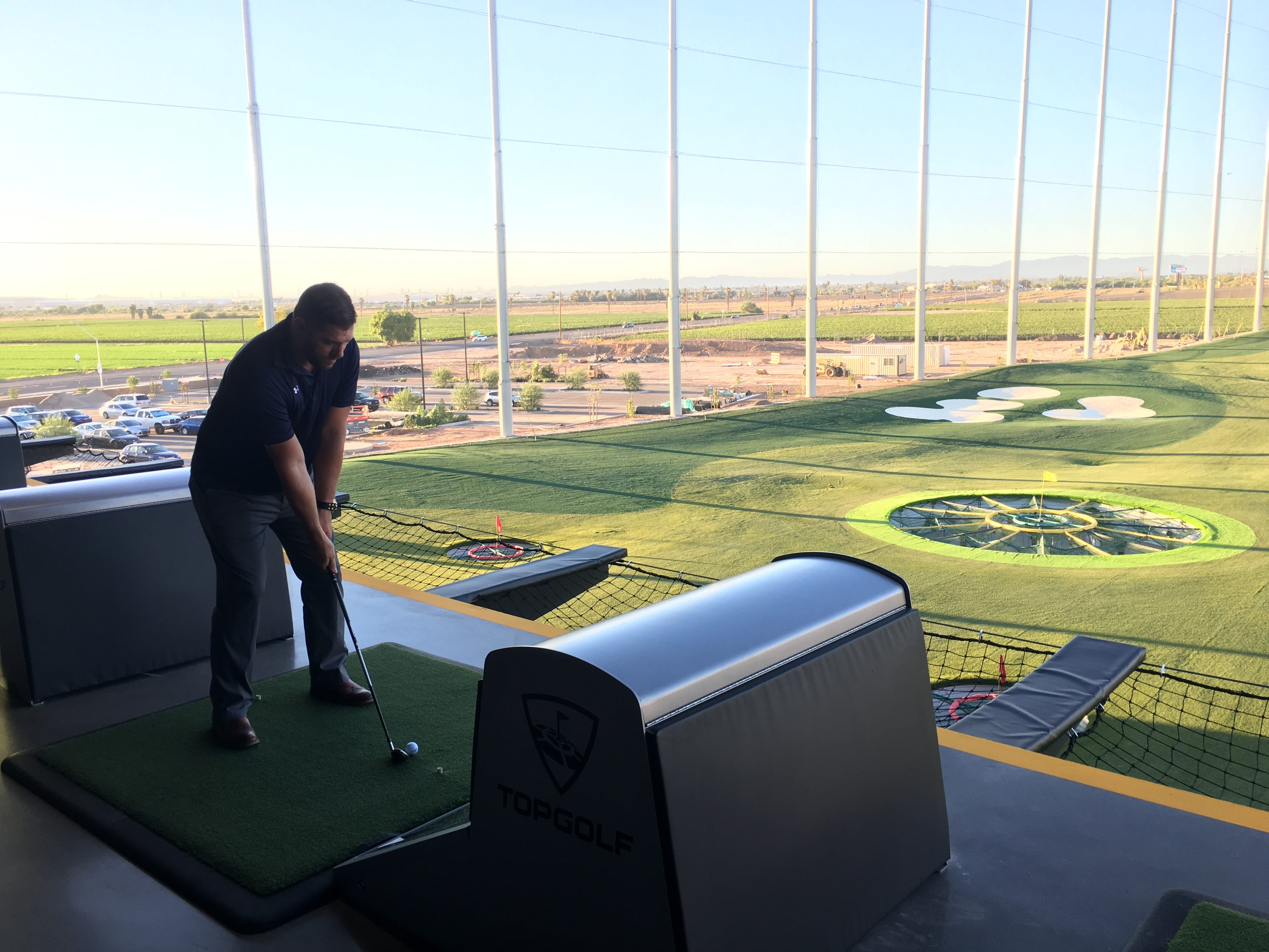 Brian Goodwin lines up a shot from one of the hitting bays at Topgolf Glendale during a tour, Sept. 12, 2018, of the newest Valley location, which is scheduled to open in September.