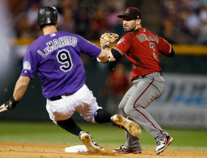 Arizona Diamondbacks third baseman Daniel Descalso, back, forces out Colorado Rockies' DJ LeMahieu at second base on the front end of a double play hit into by Nolan Armando to end the seventh inning of a baseball game Wednesday, Sept. 12, 2018, in Denver. (AP Photo/David Zalubowski)
