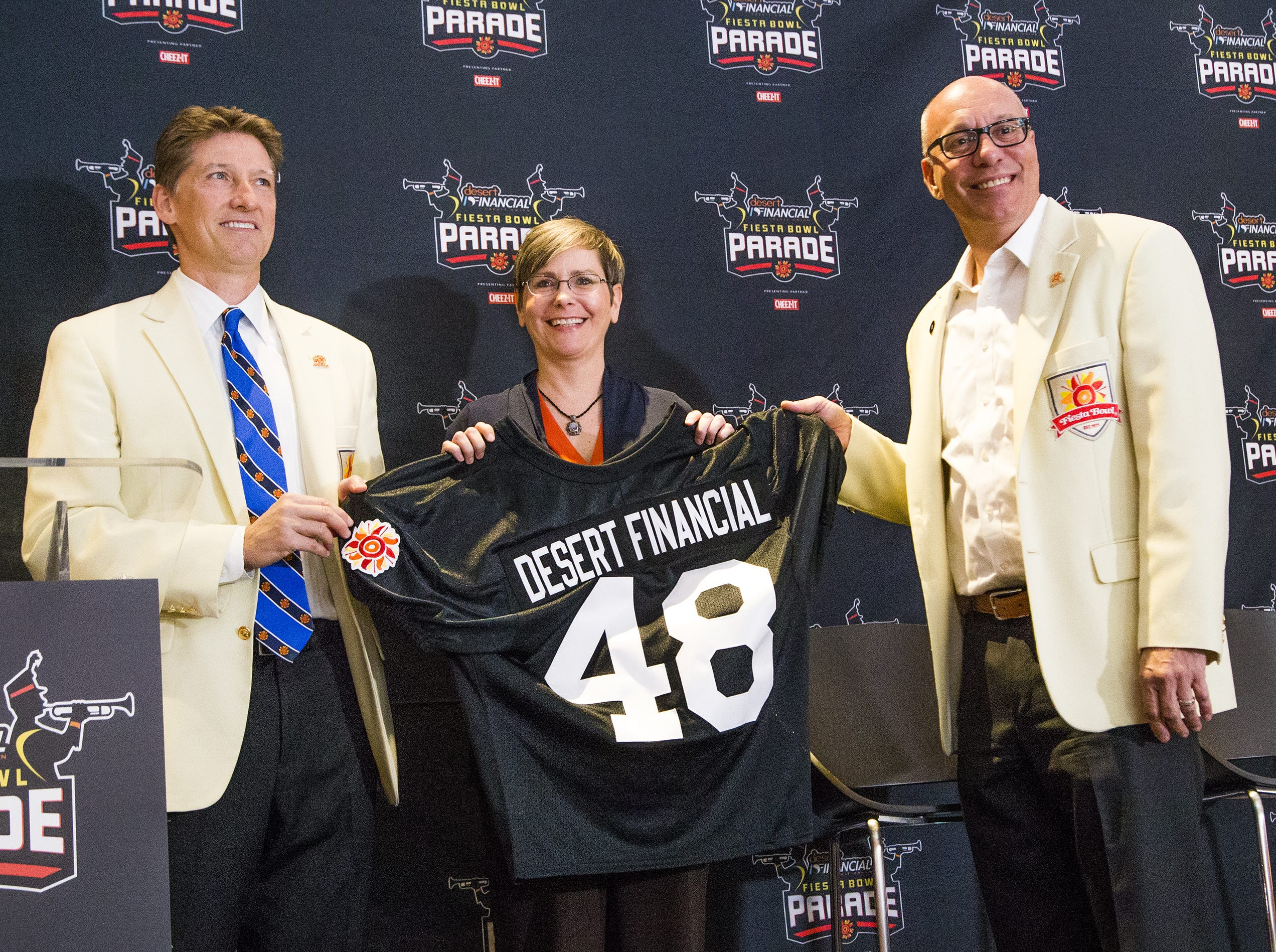 Fiesta Bowl executive director Mike Nealy, left, and chairman of the board Steve Leach, right, present Cathy Graham, senior vice president of Desert Financial Credit Union, with a jersey after it was announced that Desert Financial will be the sponsor of this year's Fiesta Bowl Parade.