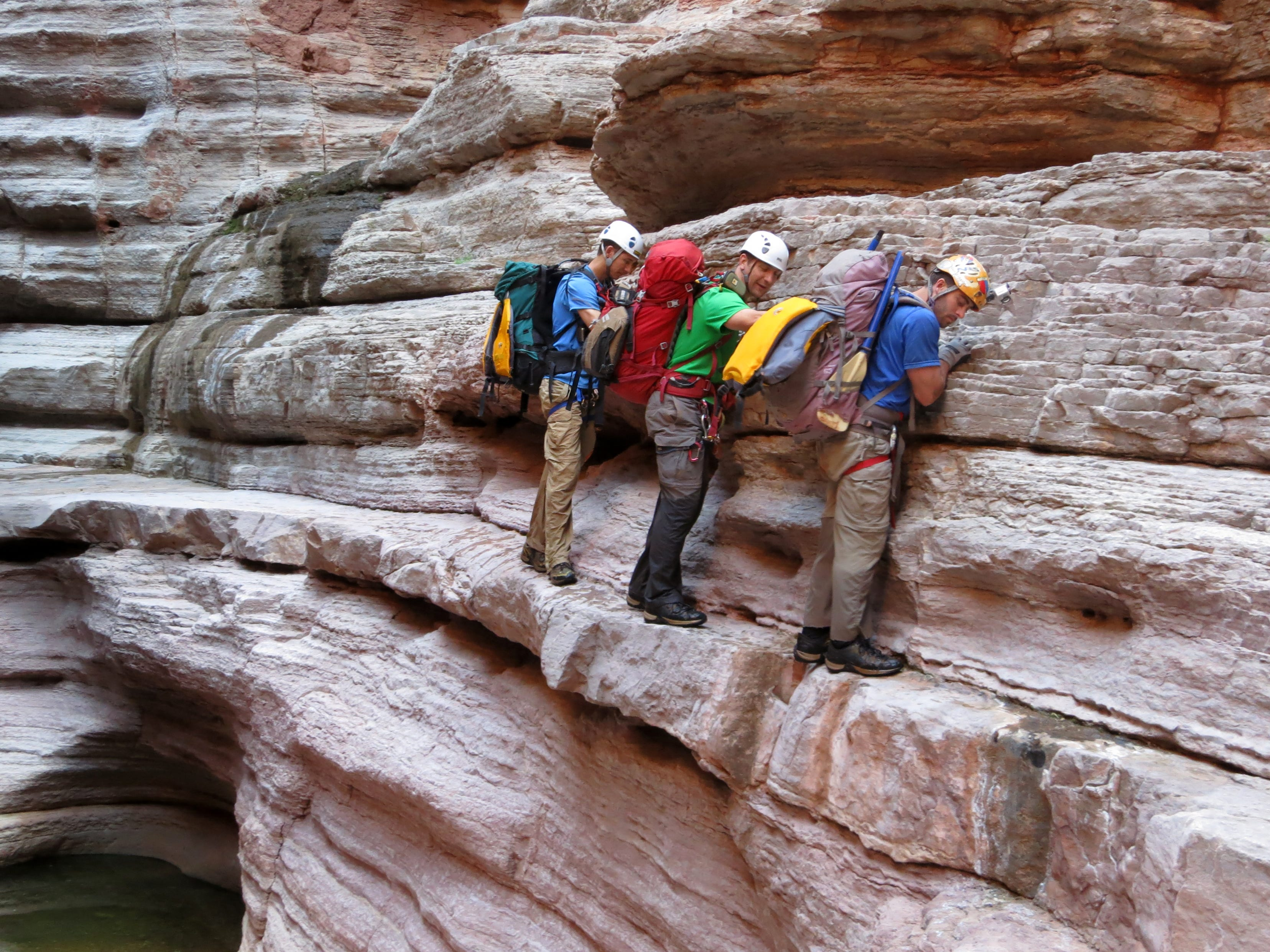 Cody Rients (from left), Mark Yarch and Eric Luth traverse muav limestone ledges while descending Olo Canyon not far from the confluence with the Colorado River in Grand Canyon National Park. Hundreds of side canyon drainages meet the Colorado River in Grand Canyon and offer a glimpse into something not impacted by Glen Canyon Dam.