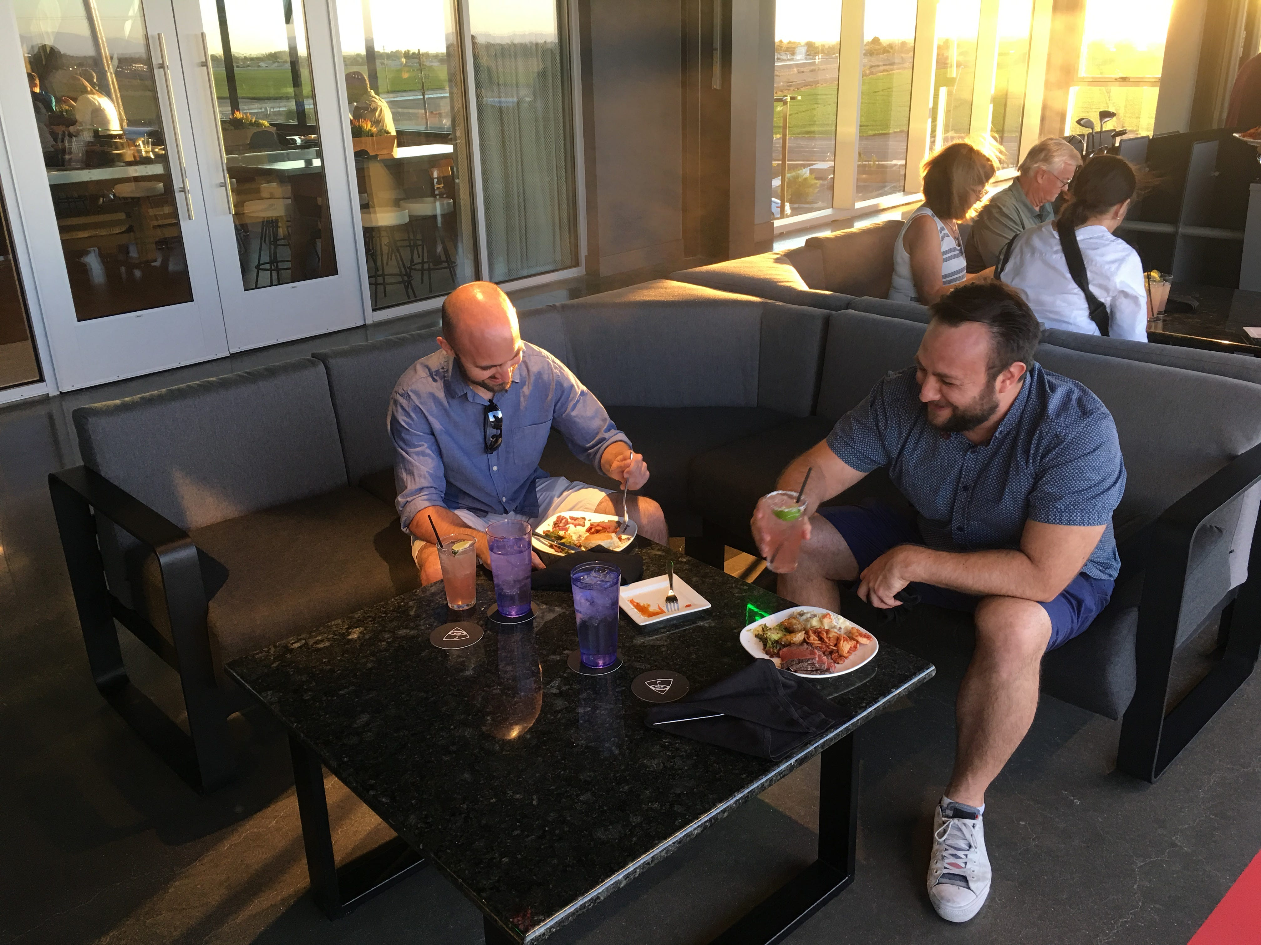 Brothers Jared and Travis Blitz enjoy a meal in one of the hitting bays at Topgolf Glendale during a tour of Topgolf's newest Valley location, Sept. 12, 2018. It's scheduled to open in September near State Farm Stadium.