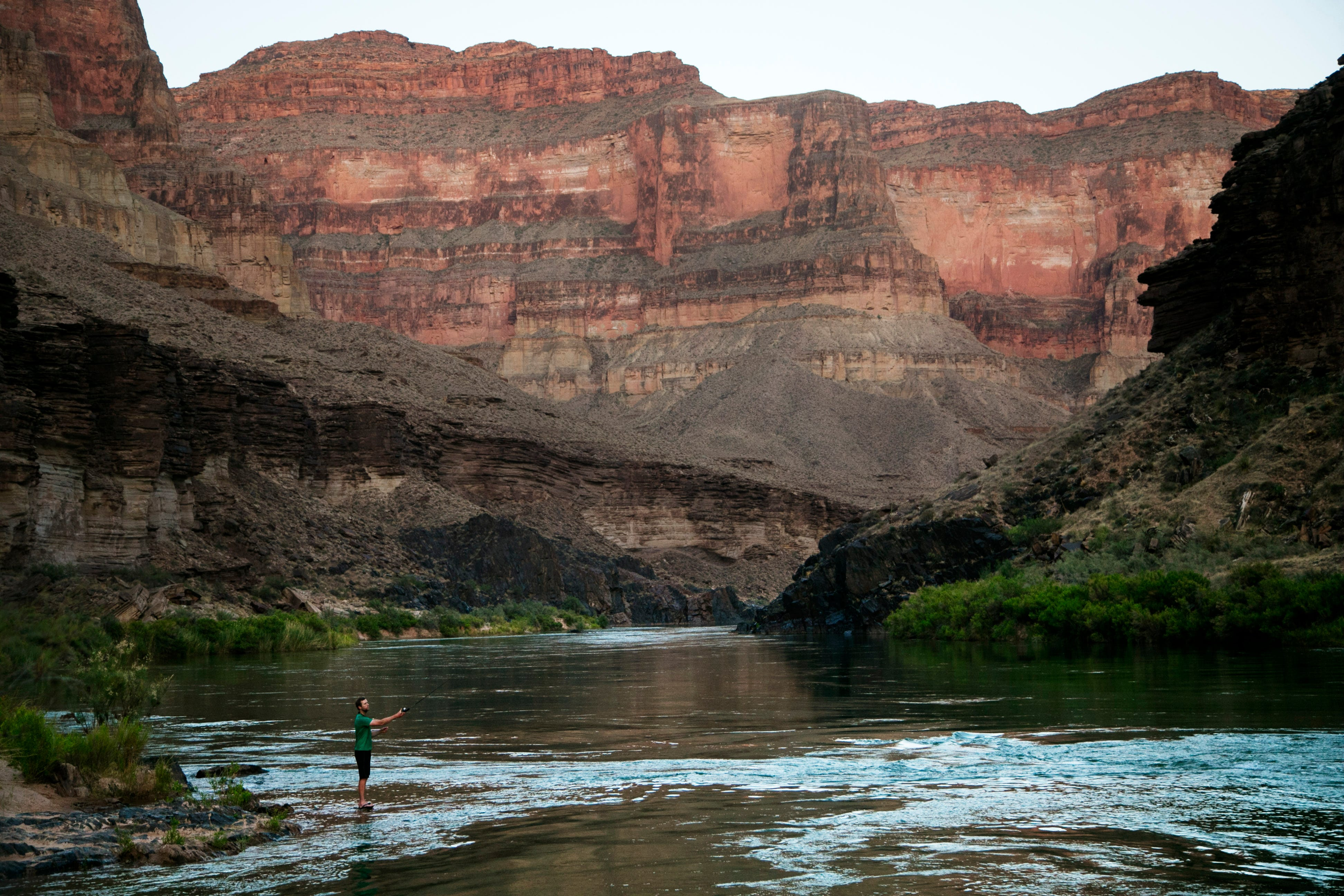 River runner Daniel Brown fishes in the Colorado River near the confluence with Blacktail Canyon in Grand Canyon National Park. Non-native trout have flourished here, and some say they've had a negative impact on the native species of fish.
