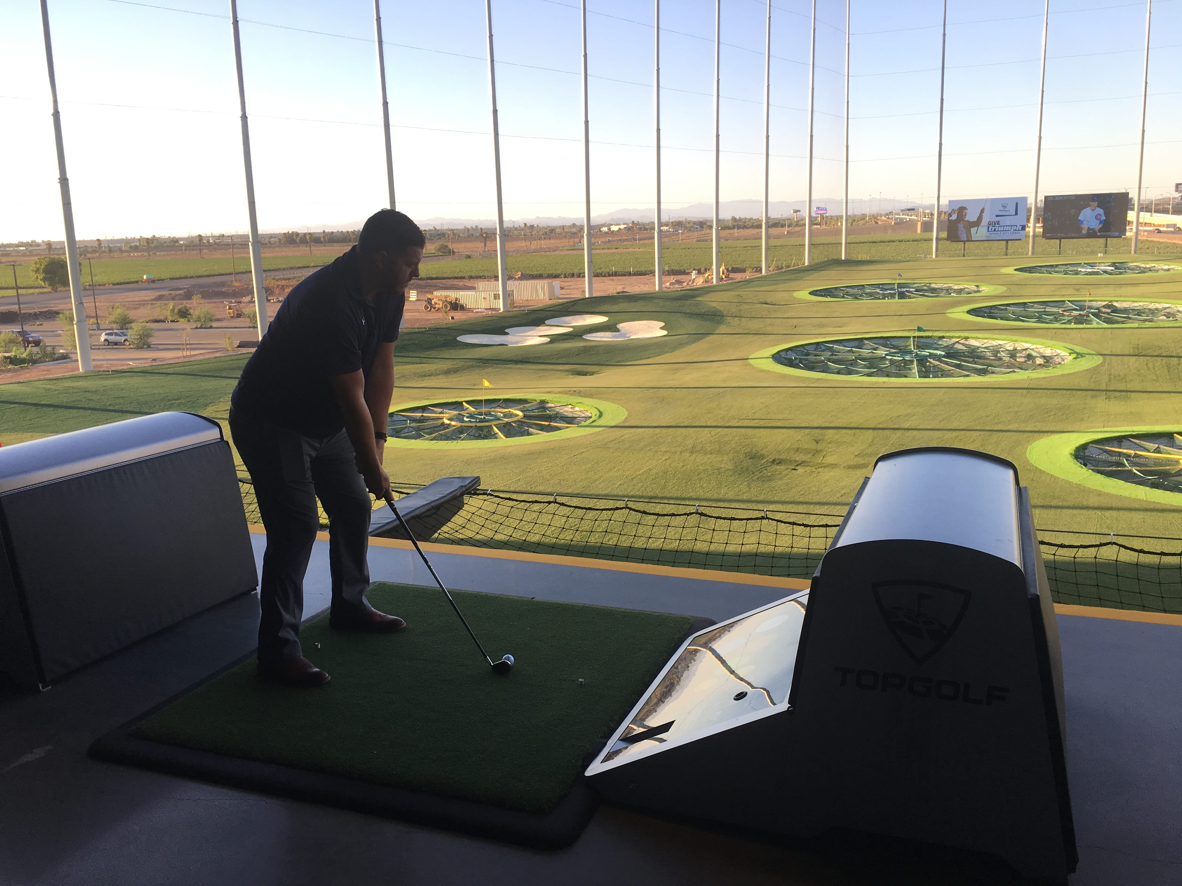 Brian Goodwin lines up a shot from one of the hitting bays at Topgolf Glendale during a tour on Sept. 12, 2018, of Topgolf's newest Valley location, which is scheduled to open in September.