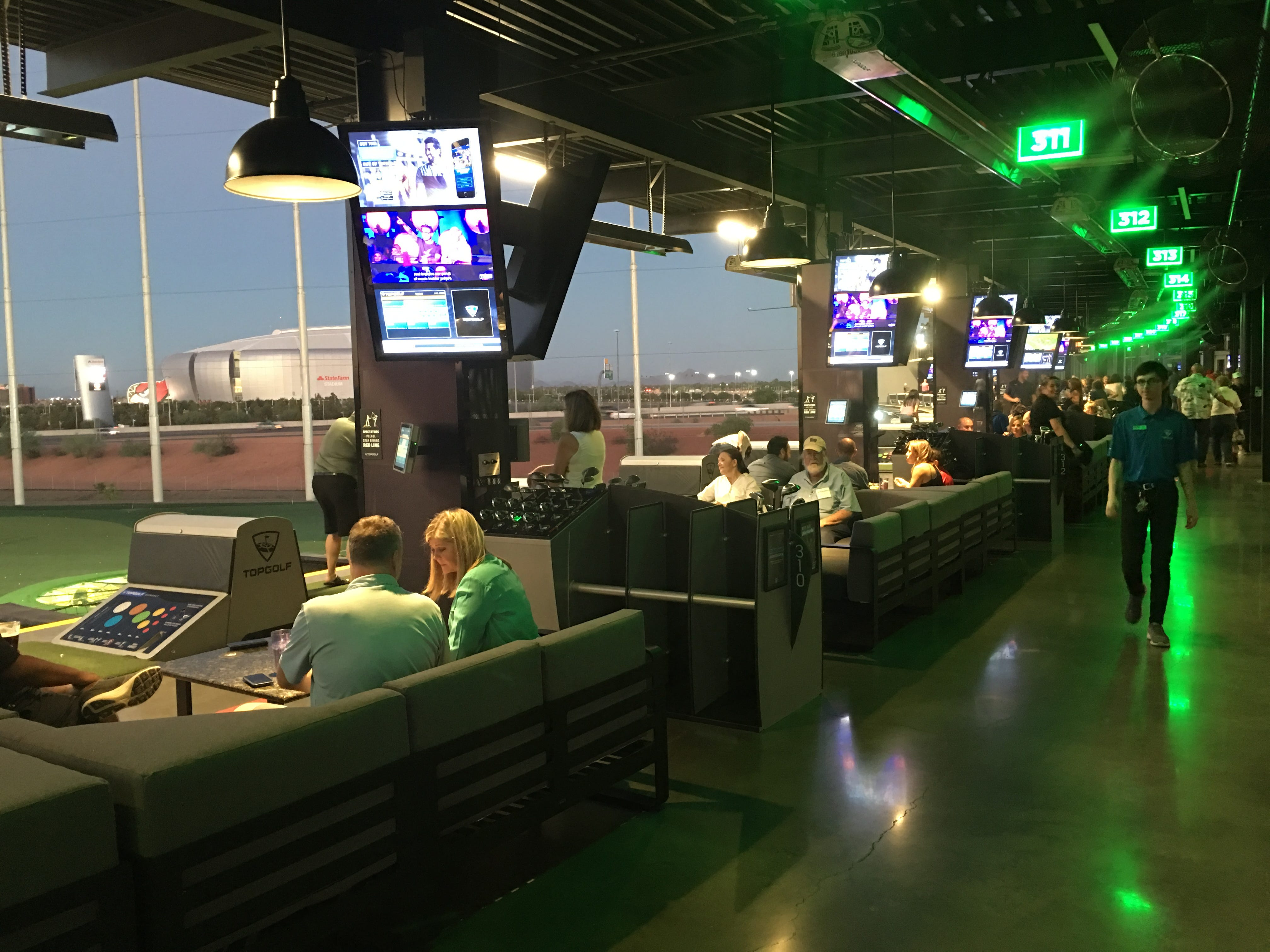 Guests attend a tour, Sept. 12, 2018, of Topgolf Glendale, the company's newest Valley location, which is scheduled to open in September near State Farm Stadium.