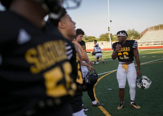 Israel Benjamin, a 17-year-old junior and running back for the Saguaro Sabercats, practices with his team at Saguaro High School in Scottsdale on Mon. Aug. 20, 2018.