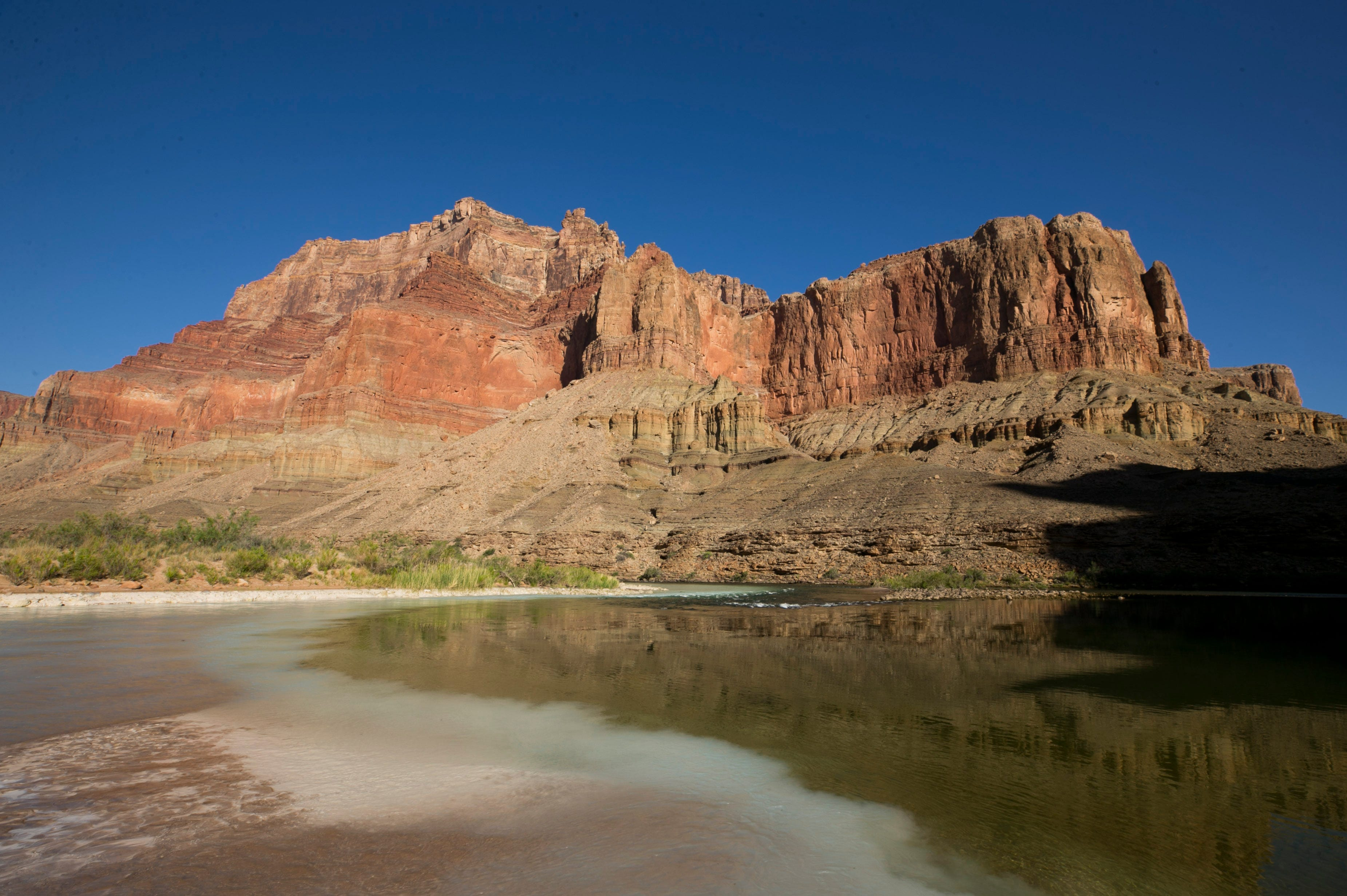 Aqua-blue, calcium carbonate-rich water from the Little Colorado River (left) mixes with water from the Colorado River in Grand Canyon National Park.