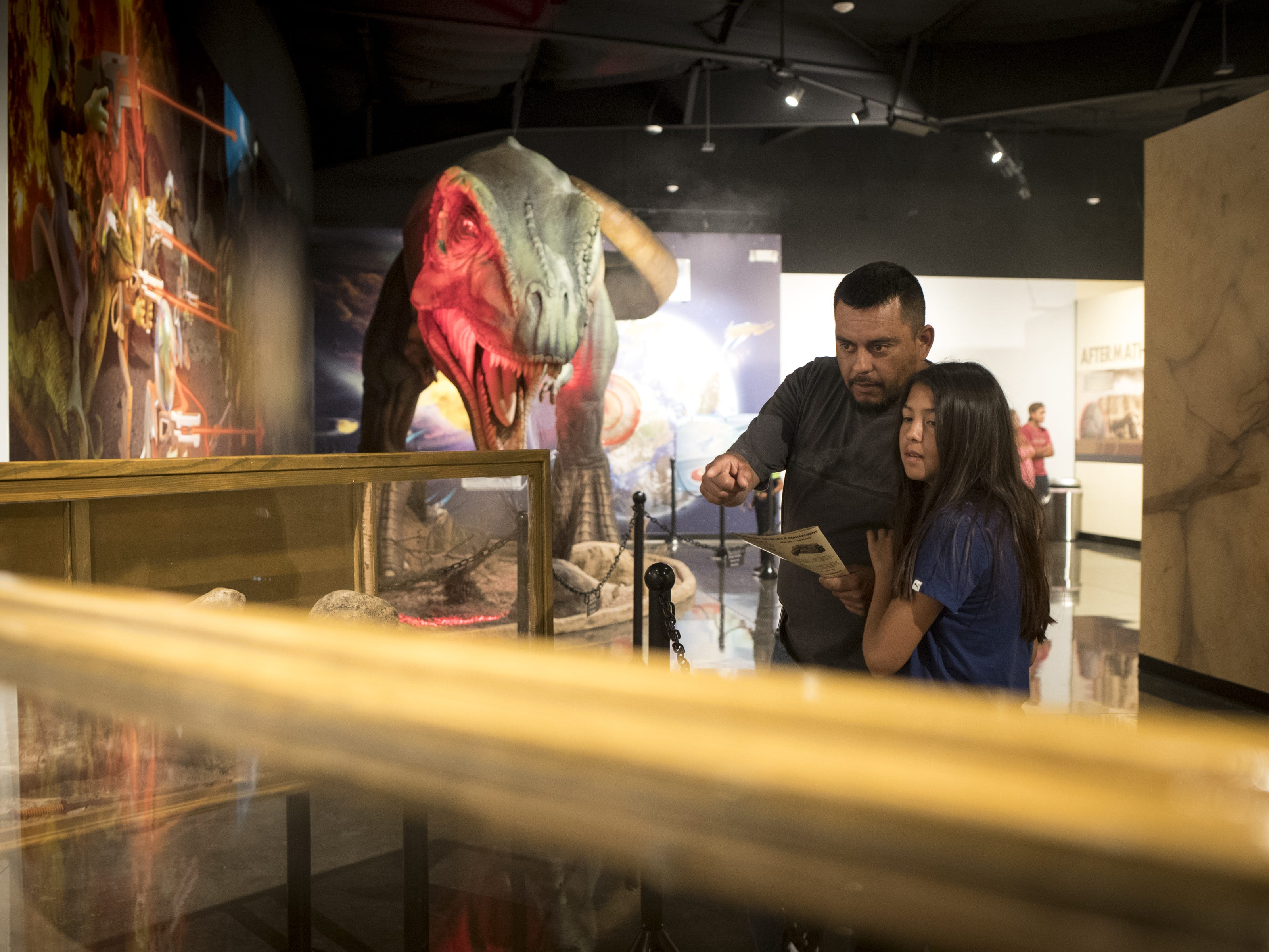 Gilbert Morales (left) and his daughter, Cynthia (11) view dinosaur bones, September 11, 2018, in the museum at the Bowlin Travel Center, east of Benson, Arizona.