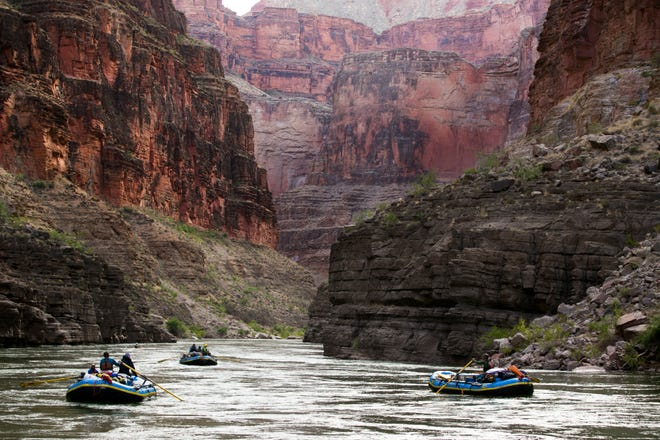 In this file photo, boats make their way down the Colorado River near river mile 151 in Grand Canyon National Park.