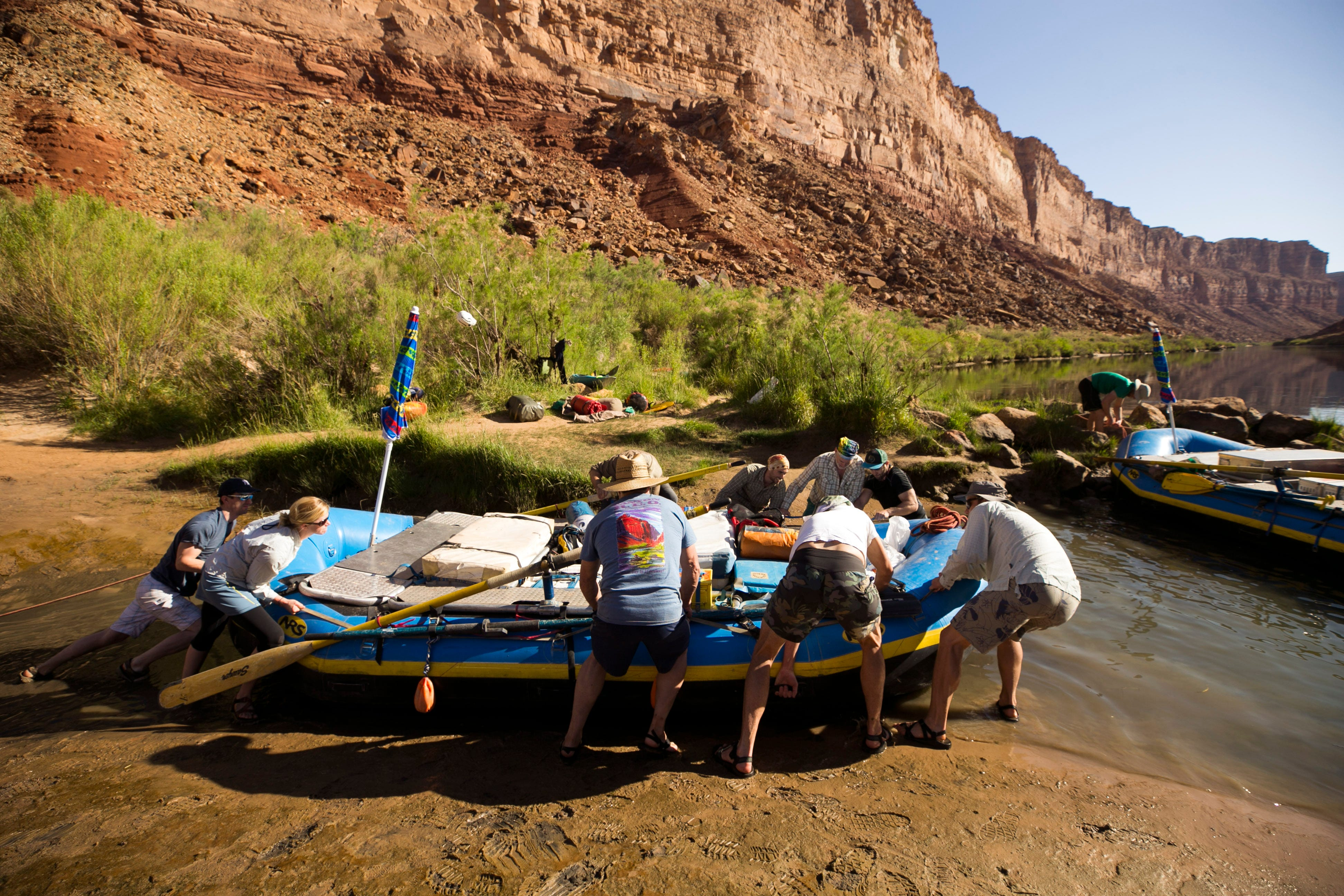 Members of a private river trip push a boat that got stuck in the mud after the Colorado River receded overnight at the campsite above Soap Creek rapid in Grand Canyon National Park.