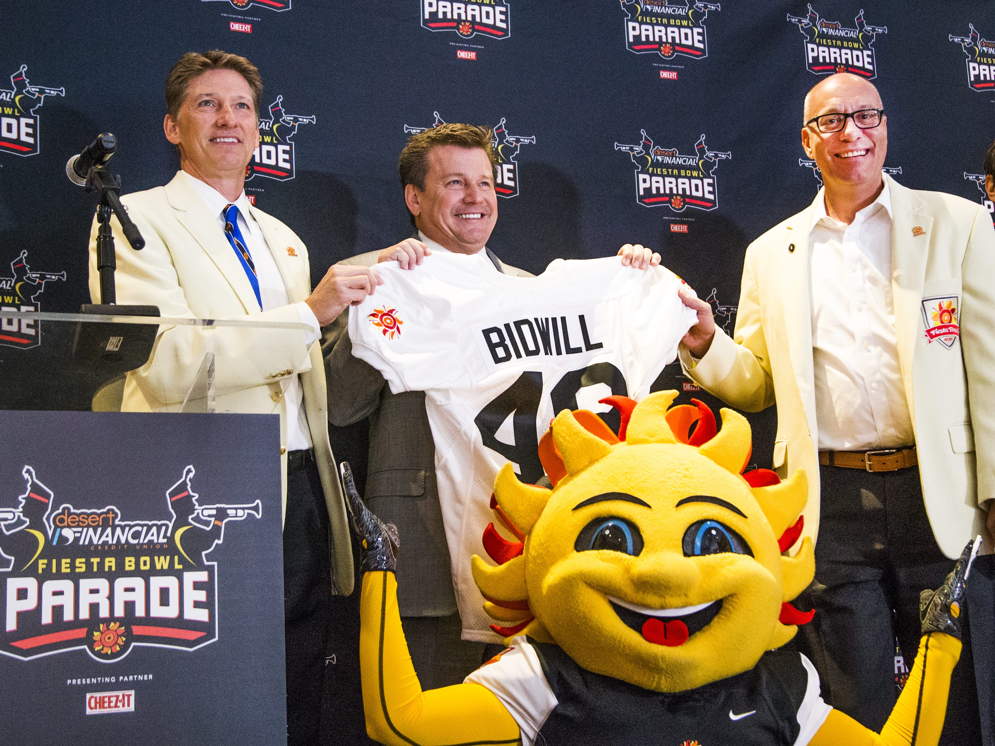 Fiesta Bowl executive director Mike Nealy, left, and chairman of the board Steve Leach, right, present Arizona Cardinals president Michael Bidwill with a jersey after it was announced that Bidwill will be the grand marshal of this year's Fiesta Bowl Parade.