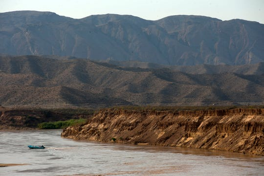 A boat goes by silt banks towering more than 50 feet above the Colorado River near Pearce Ferry.