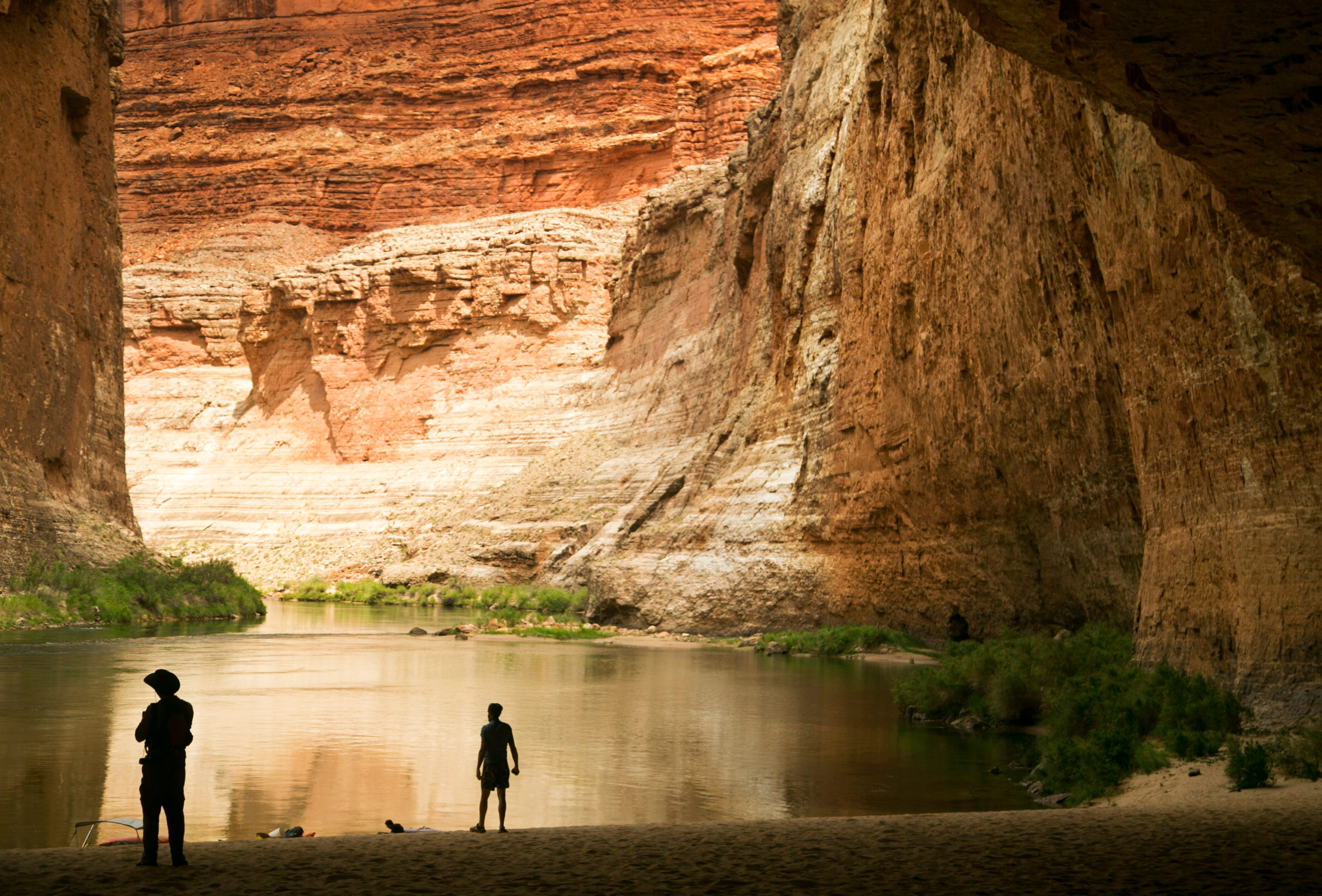 River runners stand on the banks of the Colorado River at Redwall Cavern in Grand Canyon National Park. Water releases that are meant to help rebuild beaches and sandbars in the Canyon often turn up mixed results.