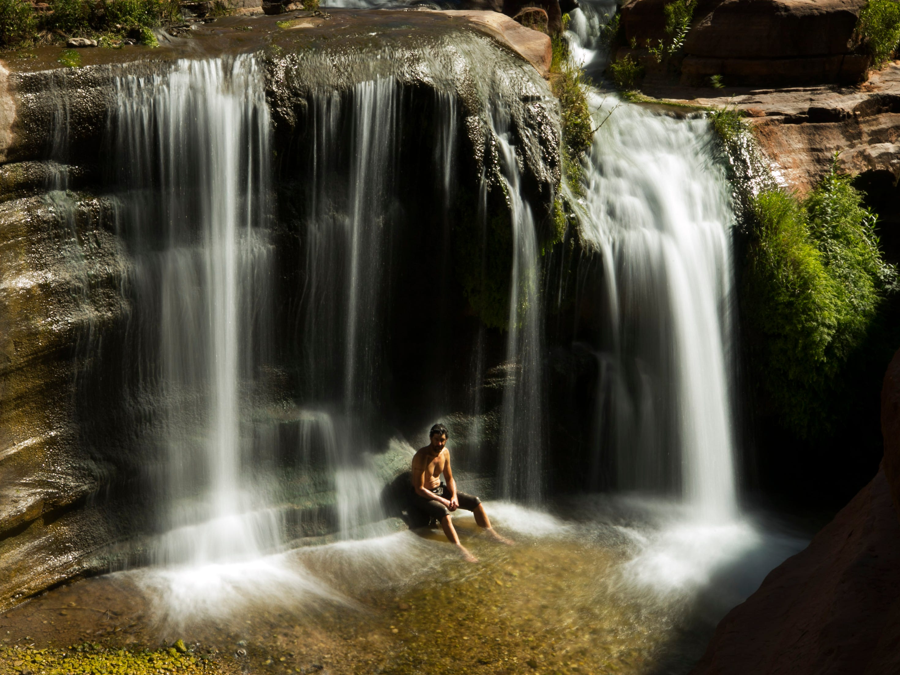 Ezra Jones sits at the base of a waterfall atop the Tapeats sandstone narrows of Deer Creek not far from the confluence with the Colorado River in Grand Canyon National Park. Hundreds of side canyon drainages meet the Colorado River in Grand Canyon and offer a glimpse into something not impacted by Glen Canyon Dam.