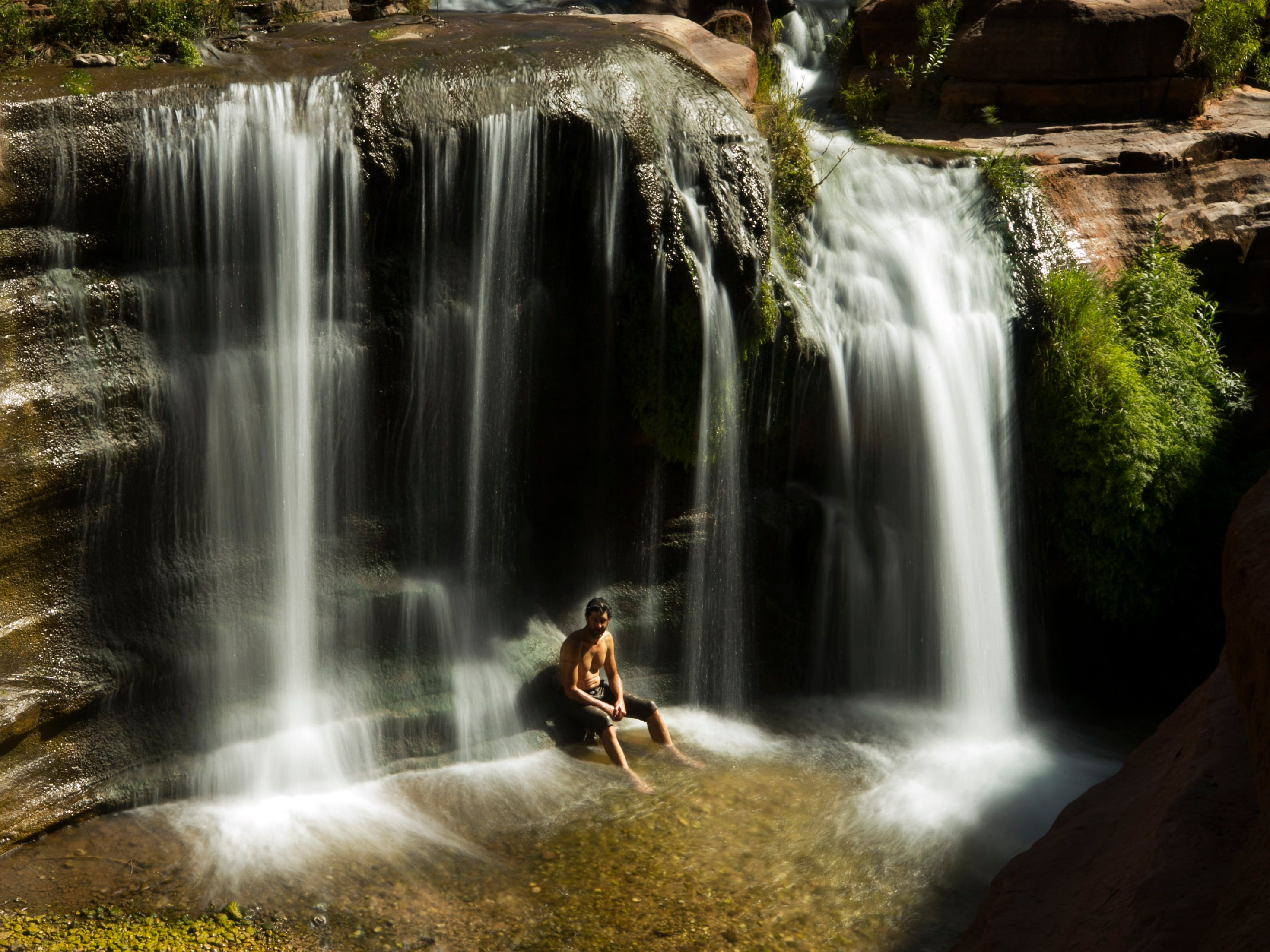 Ezra Jones sits at the base of a waterfall on May 26, 2018, atop the Tapeats sandstone narrows of Deer Creek not far from the confluence with the Colorado River in Grand Canyon National Park. Hundreds of side canyon drainages meet the Colorado River in Grand Canyon and offer a glimpse into something not impacted by Glen Canyon Dam.