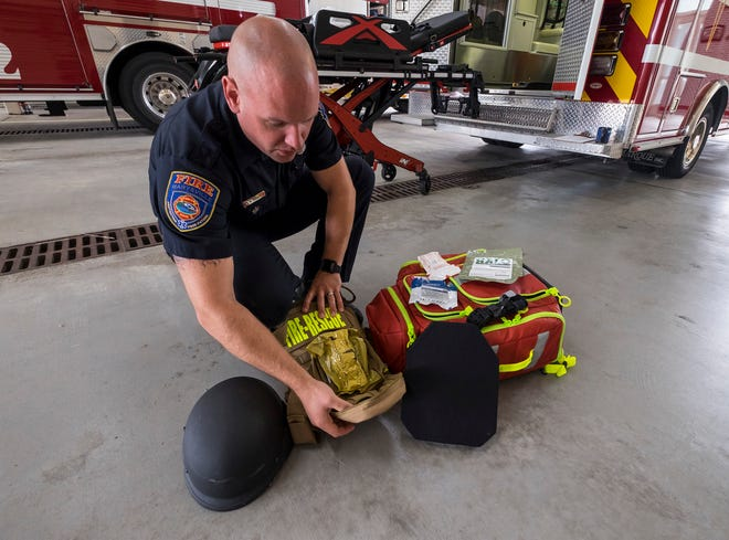 Marysville firefighter paramedic Matt Reeves  opens an individual first aid kit attached to a piece of chest armor Thursday, Sept. 13, 2018, at the Marysville Fire Department.  The armor is equipped with level 4 plates, which can withstand a shot from most common rifles.