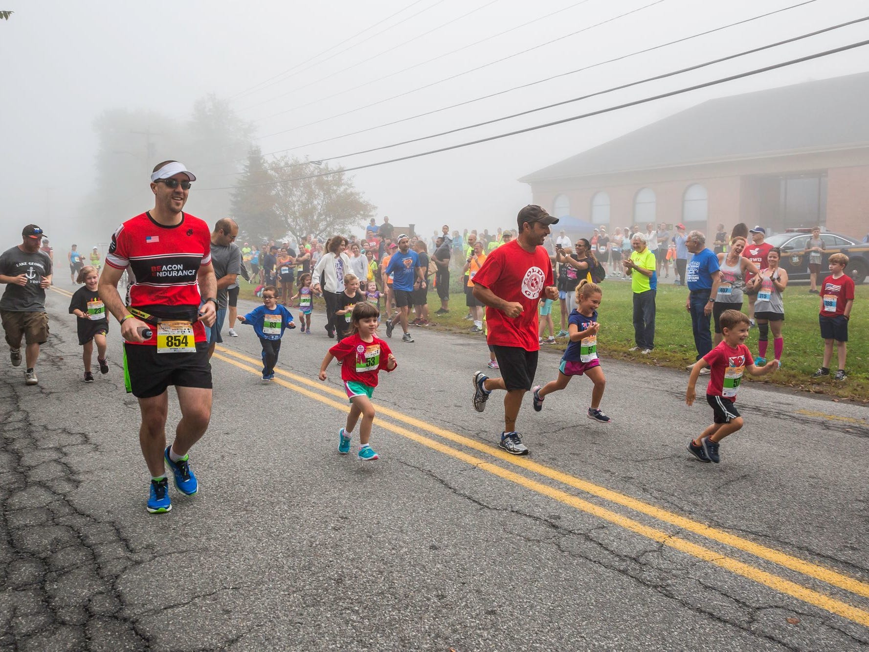 Adults run alongside the youngest of the kids mile runners in LaGrangeville during the Dutchess County Classic in September 2017.