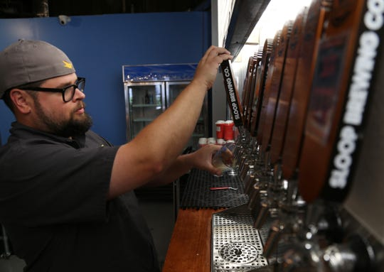 Sloop Brewing's director of sales and marketing Joe Turco pours a pint of Juice Bomb IPA at Sloop's new location in East Fishkill on Sept 13, 2018.