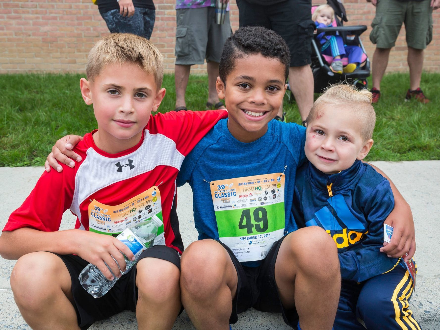 Kids' mile boys winner Noah Mellen, center, sits with Reese Steinhous and Oliver Mellen after the kids mile race last September.
