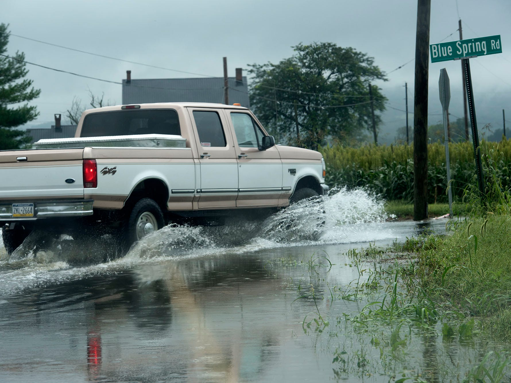 A truck drives through a flooded Corner Road in Mercersburg. A bridge was destroyed and there is street flooding and road closings around Shimpstown Road in the Mercersburg area on Thursday, September 13, 2018.