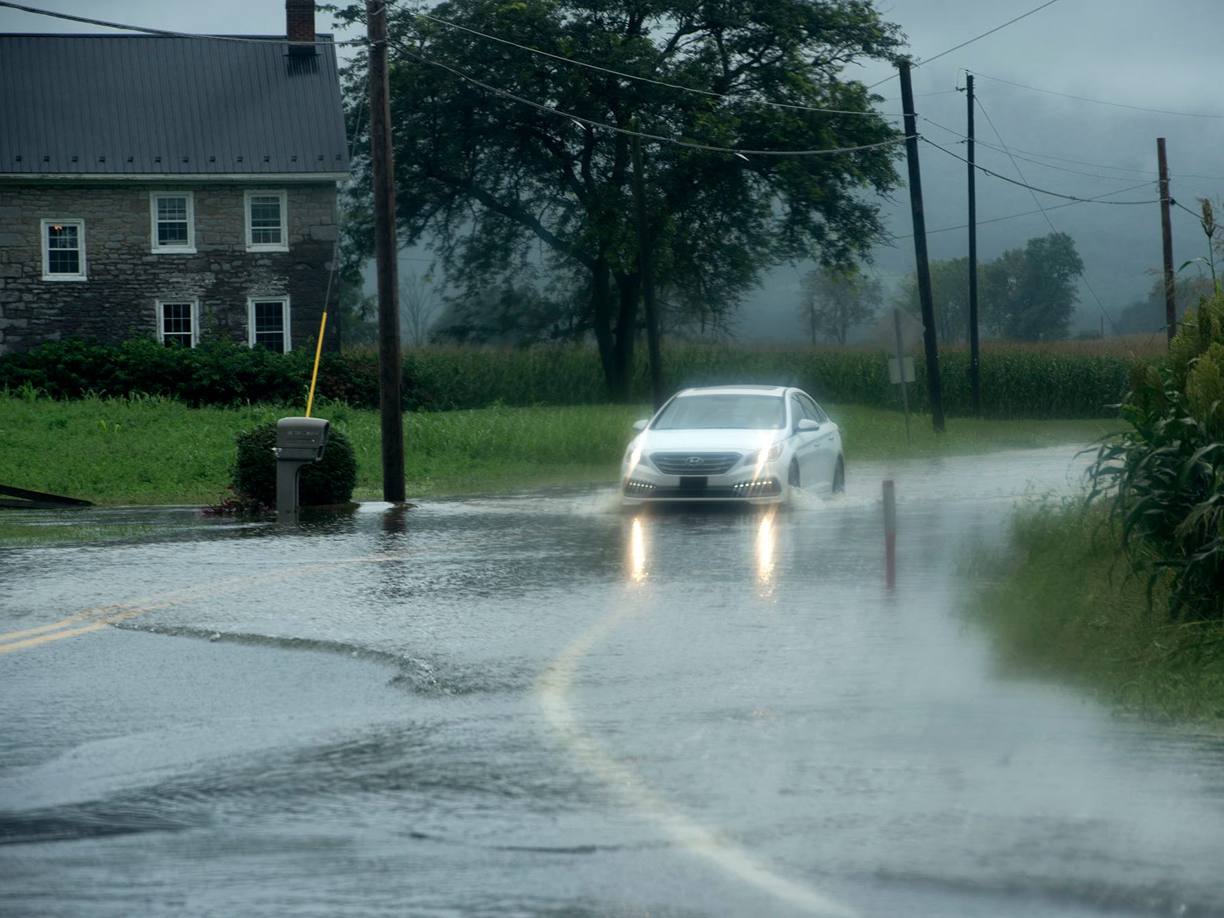 A car travels through a flooded roadway at Corner Road. A bridge was destroyed and there is street flooding and road closings around Shimpstown Road in the Mercersburg area on Thursday, September 13, 2018.