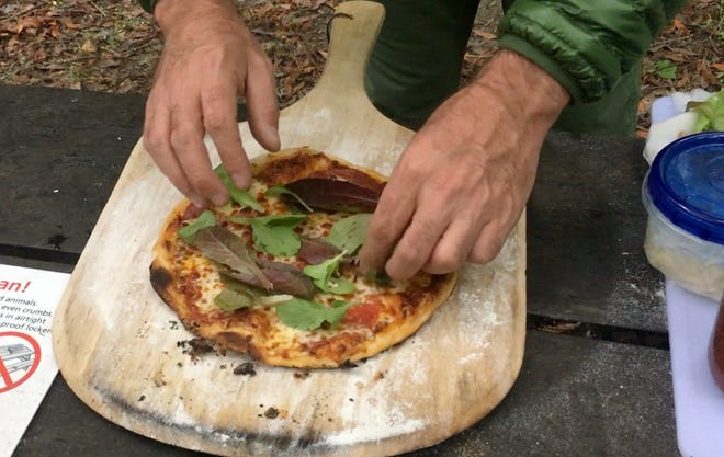 Outdoors writer Benjamin Spillman places fresh greens on a pizza he made while camping.