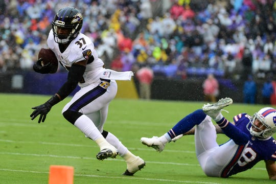 Baltimore Ravens running back Javorius Allen (37) runs past Buffalo Bills defensive back Phillip Gaines (28) during the first quarter at M&T Bank Stadium.