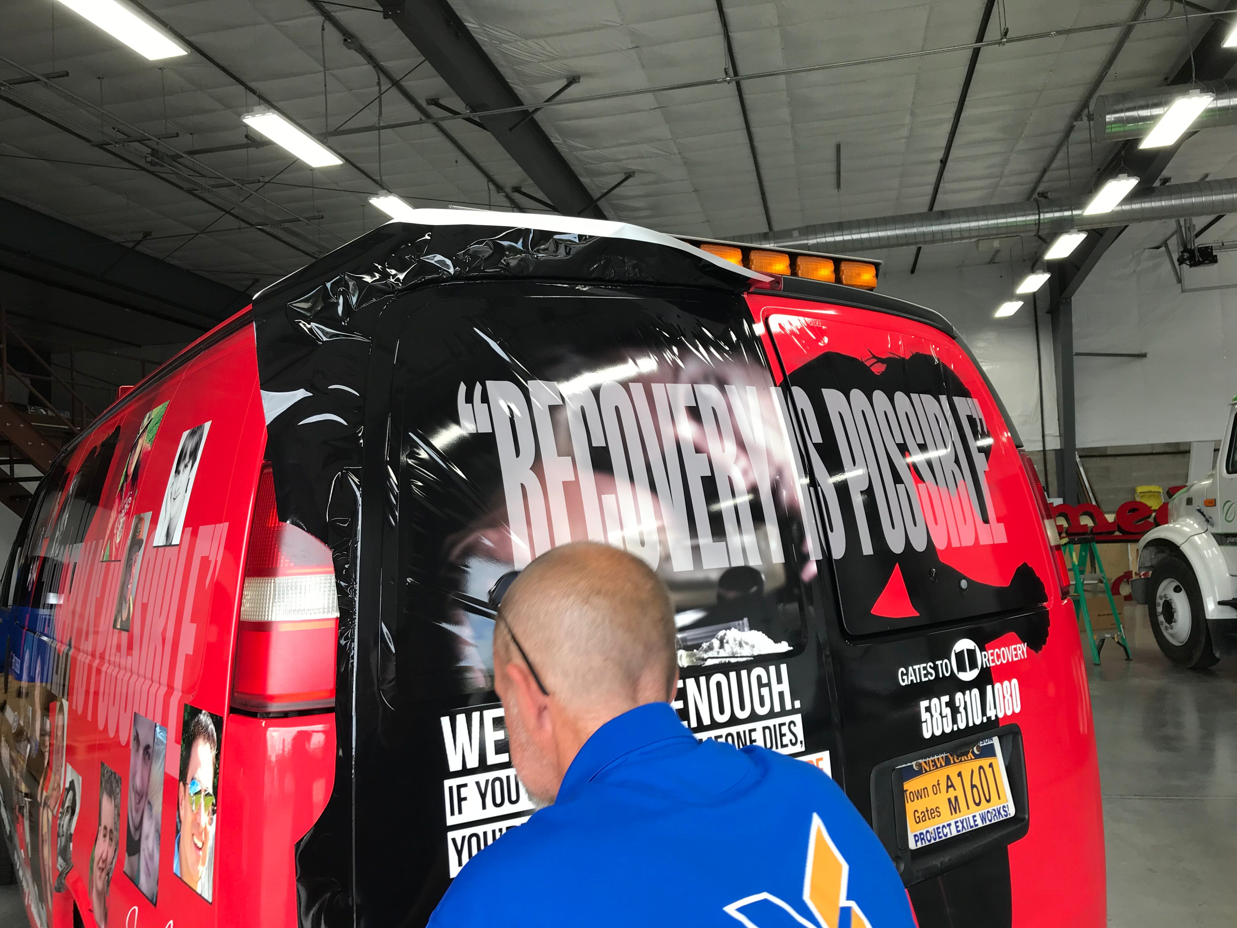 An employee of Vital Signs in Webster puts finishing touches on a van that Gates Police will use to raise awareness of the people caught up in the opioid epidemic.