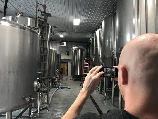 Dan Moriarty, Stoneyard director of social media, photographs the new equipment at Stoneyard Brewing in Brockport.