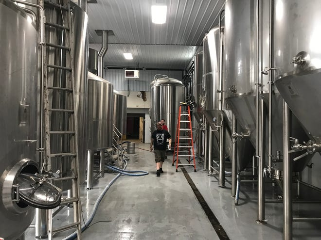 Stoneyard assistant brewer James Riley III inspects the new fermentation vessels at the brewery's production space in Brockport.