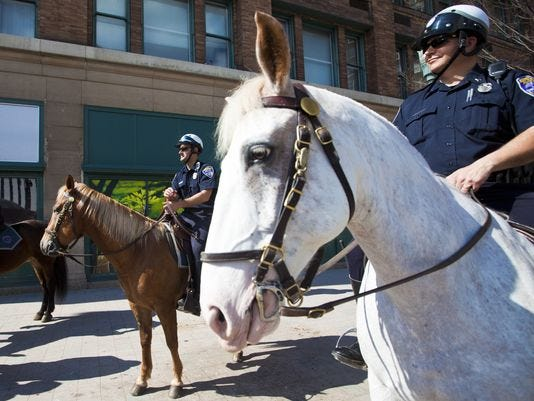 From 2012: In front, Rochester Police Officer Scott Wehr rides Raffi near downtown's Liberty Pole. At left, Officer Eric Smith rides Buddy.