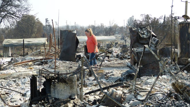 Zita Harrington Biehle walks through the charred remains of her Lake Keswick Estates home.