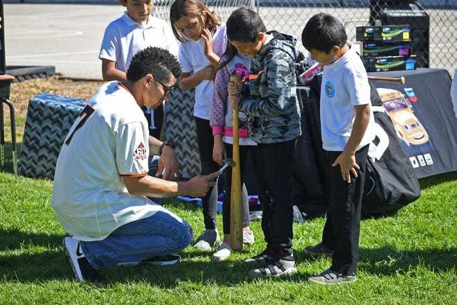 San Francisco Giants center fielder Gorkys Hernandez shows how different parts of a baseball bat vibrate when hit with a hammer to Roosevelt Elementary School students.