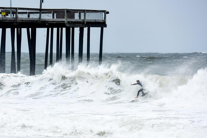 Robby Pinzhoffer of Ocean City catches a wave at the Ocean City inlet. The area experienced mild flooding, wind and rough surf on Thursday, Sept 13.