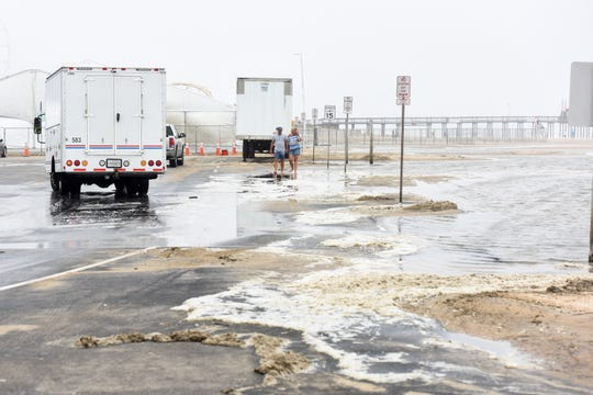 Visitors walk through flooding in the parking lot at Ocean City inlet on Thursday, Sept 13.
