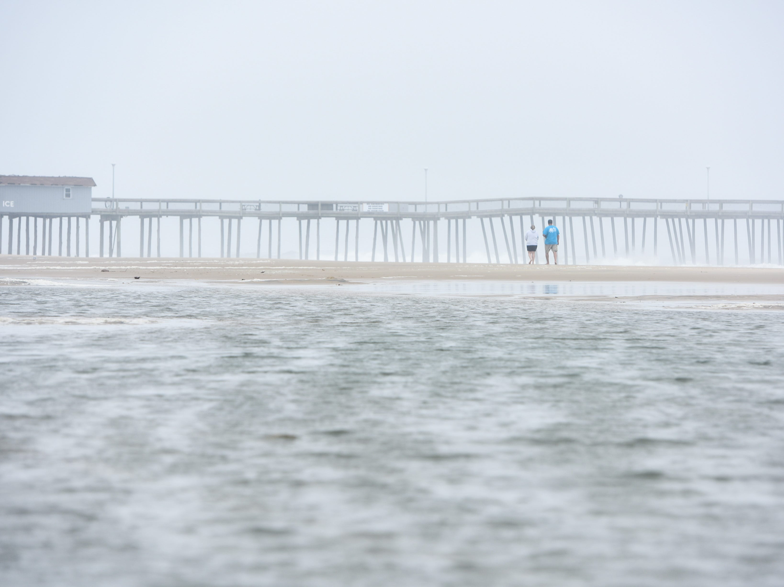 Visitors walk on the beach at the Ocean City inlet. The area experienced mild flooding, wind and rough surf on Thursday, Sept 13.